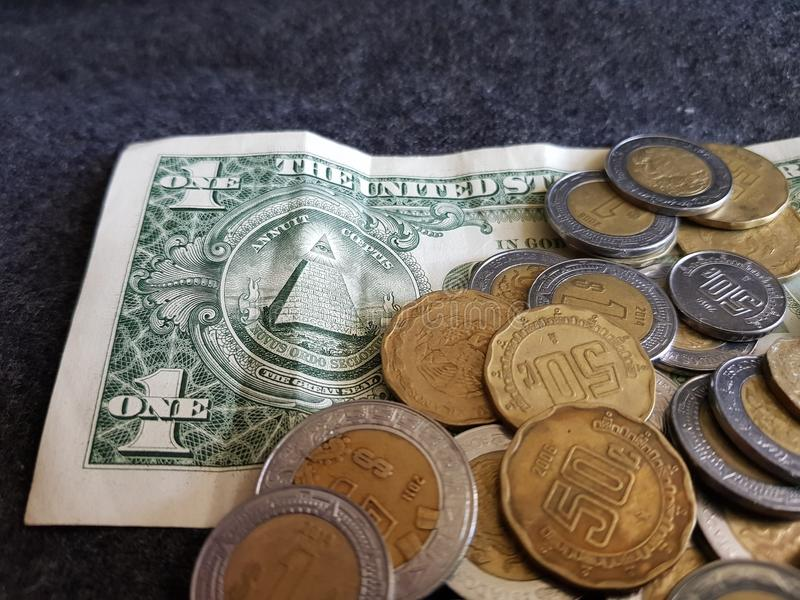 dorso de un billete de dólar y monedas de Pesos mexicanos imagenes de archivo