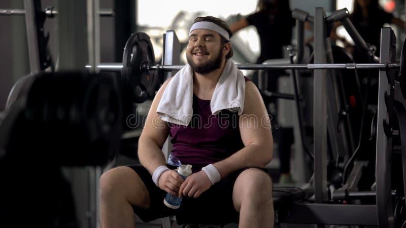 Dorstig gelukkig mensen drinkwater na uitputtende opleiding, de training van het gewichtsverlies stock afbeelding
