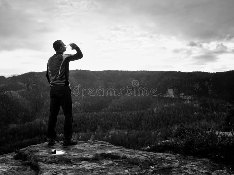 Dorstige wandelaar in blauwe en zwarte sportkleding met fles water Zwetende vermoeide toerist op de piek van zandsteen rotsachtig royalty-vrije stock afbeelding