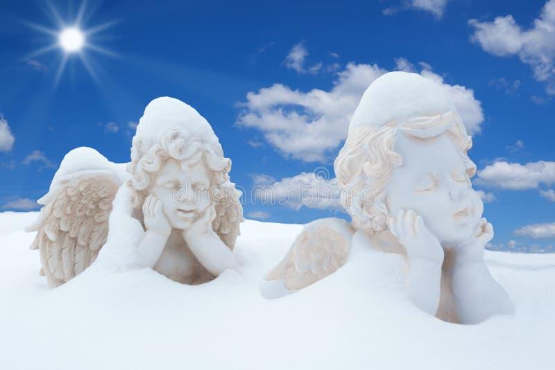 Dos ángeles nevosos en la sol imagen de archivo