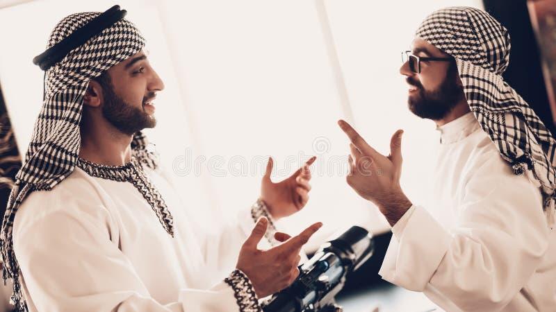 Dos árabes cerca del telescopio que mira en uno a fotos de archivo