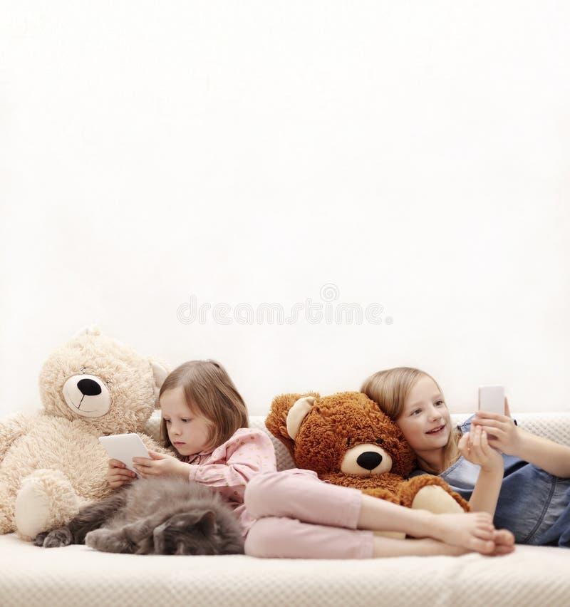 Dos años de las hermanas 7 y 8 de las niñas están mirando un eBook y un smartphone en casa en el sofá con su gato foto de archivo libre de regalías