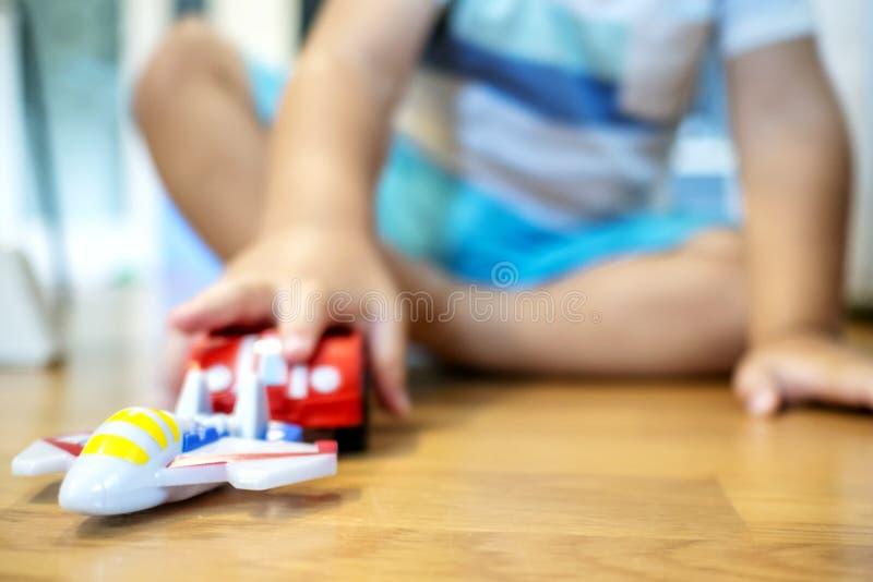 Dos años del muchacho están jugando con sus juguetes dentro fotografía de archivo libre de regalías