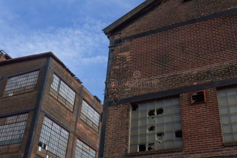 Dos abandonaron edificios industriales contra un cielo azul imagen de archivo libre de regalías