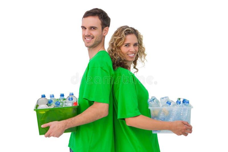 Dos activistas sonrientes que llevan a cabo la caja de recyclables y de vagos derechos foto de archivo