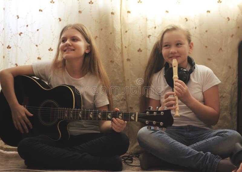 Dos adolescencias femeninas que tocan los instrumentos musicales, guitarra y flauta, sentándose en el piso en casa foto de archivo libre de regalías