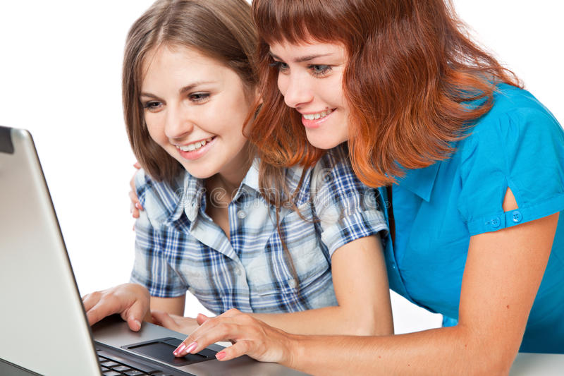 Dos adolescente-muchachas con la computadora portátil imagen de archivo