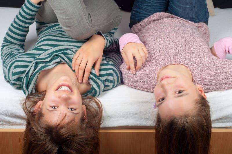 Dos adolescentes bonitos que mienten en cama fotos de archivo