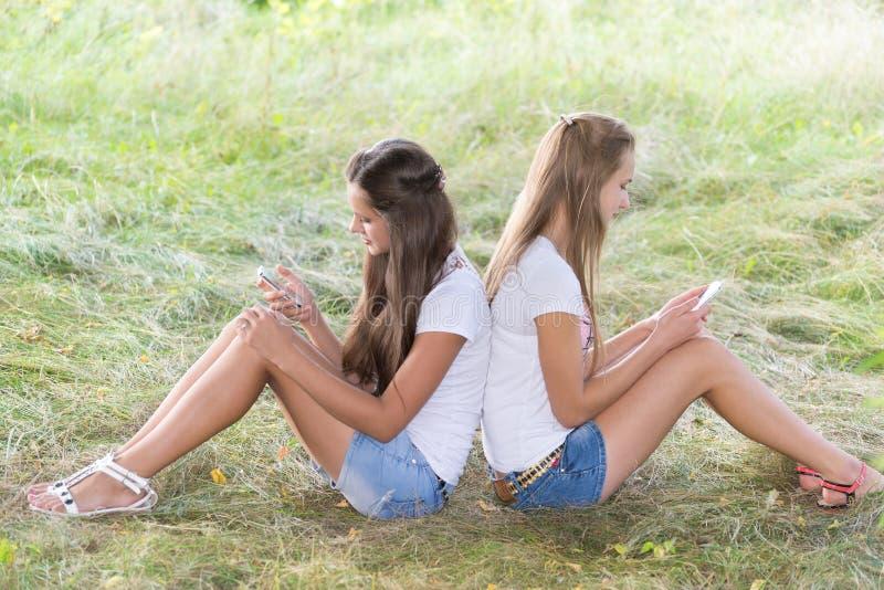 Dos adolescentes con los teléfonos celulares se están sentando en hierba foto de archivo