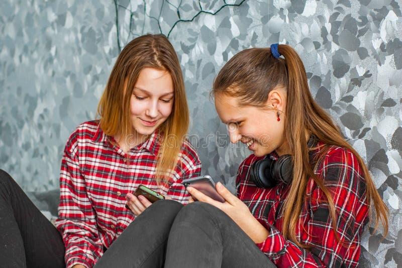 Dos adolescentes jovenes que usan los tel?fonos m?viles mientras que se sienta en un sof? en casa fotos de archivo
