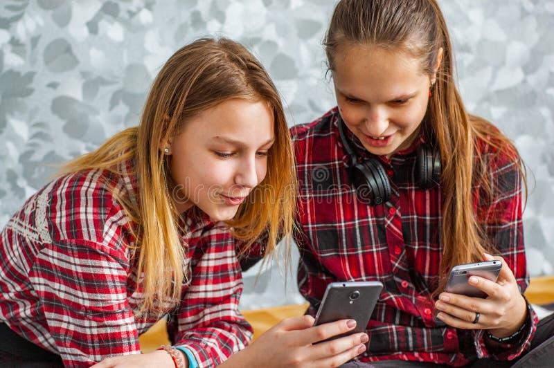 Dos adolescentes jovenes que usan los tel?fonos m?viles mientras que se sienta en un sof? en casa foto de archivo