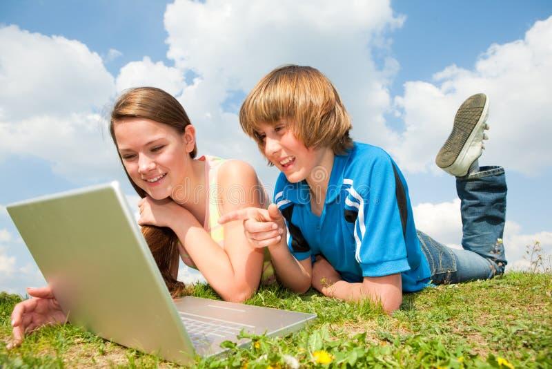 Dos adolescentes sonrientes con la computadora portátil imagenes de archivo