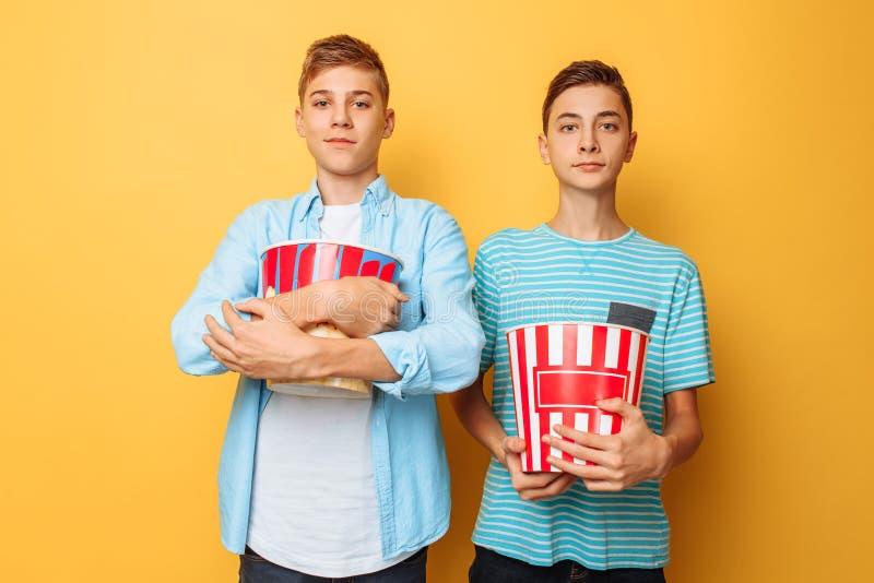 Dos adolescentes, sosteniendo un cubo de palomitas en sus manos, se están preparando para mirar una película, en un fondo amarill fotos de archivo