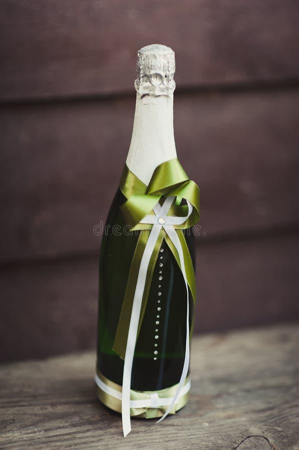 Dos adornaron las botellas de champán y de brandy como novia y novio en la tabla de cena de boda imagen de archivo libre de regalías