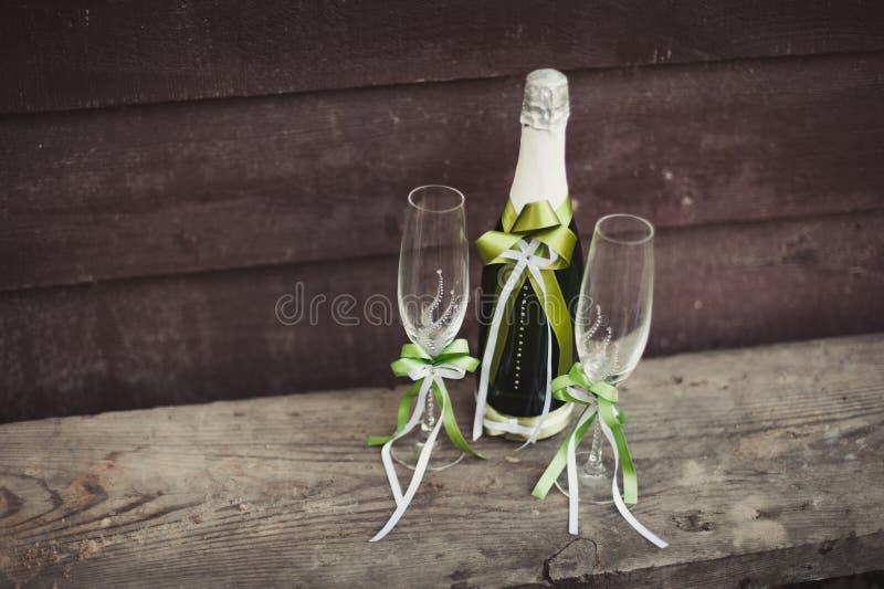 Dos adornaron las botellas de champán y de brandy como novia y novio en la tabla de cena de boda foto de archivo