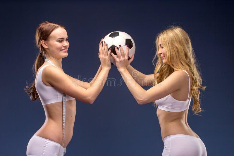 Dos aficionados al fútbol hermosos adentro sostienen el balón de fútbol imagen de archivo libre de regalías