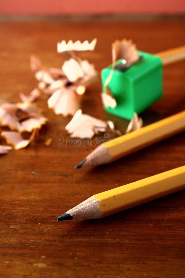 Dos afilaron los lápices y uno en sacapuntas de lápiz fotos de archivo libres de regalías