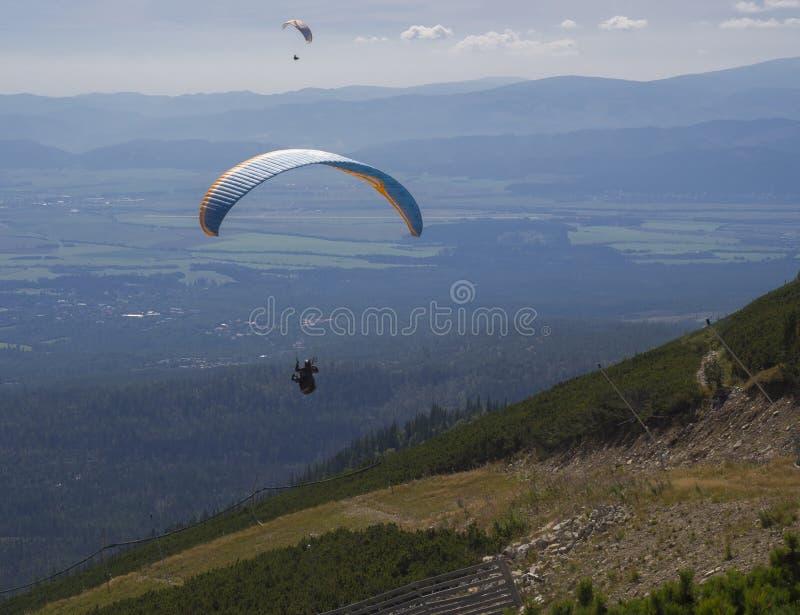Dos alas flexibles vuelan sobre un valle de la montaña en un día de verano soleado Kiting en cometa azul y anaranjada en montañas fotografía de archivo