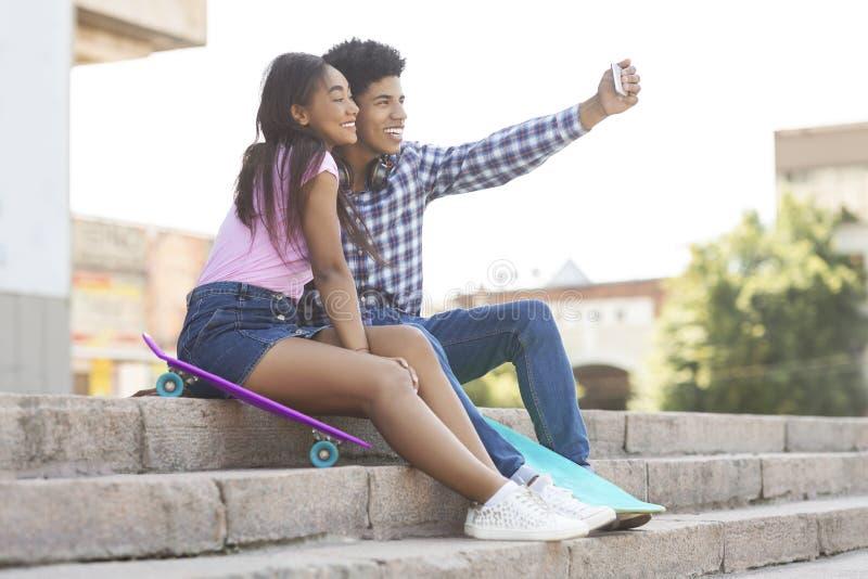 Dos alegres adolescentes africanos tomándose selfie al aire libre foto de archivo libre de regalías