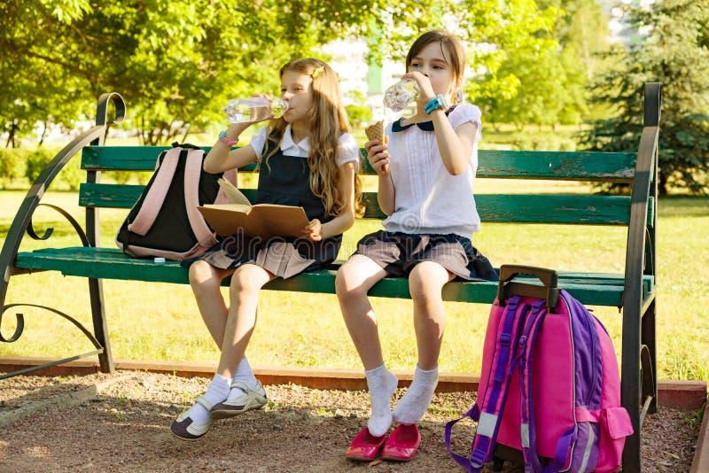Dos alumnos de las niñas beben el agua de la botella el día soleado, sentándose en el parque fotografía de archivo libre de regalías