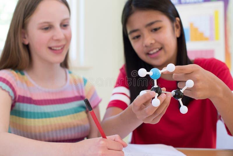 Dos alumnos femeninos que usan a Kit In Science Lesson modelo molecular imagen de archivo