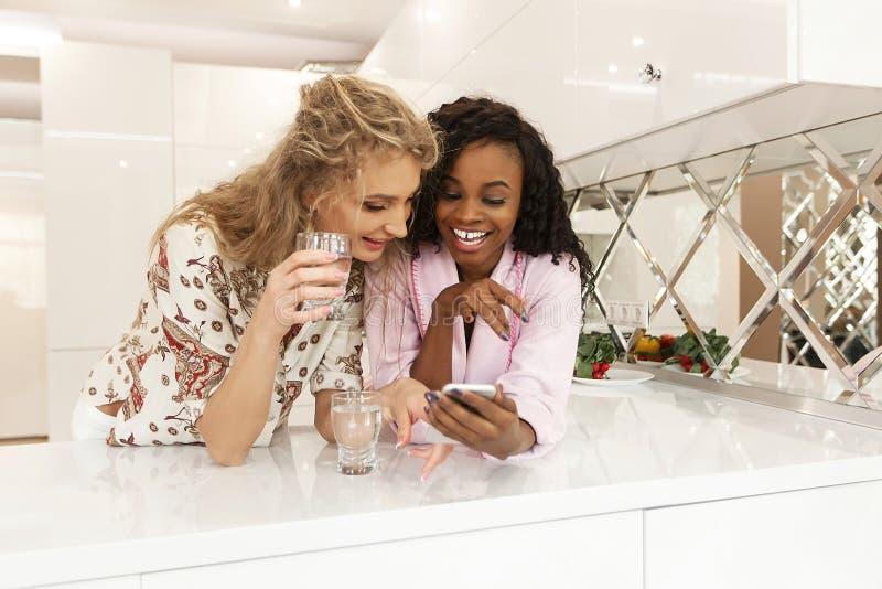Dos amigas africanas y caucásicas hermosas jovenes que ríen mientras que mira la pantalla móvil imágenes de archivo libres de regalías