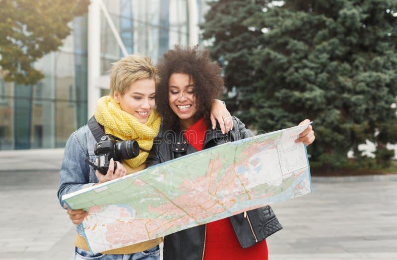 Dos amigas al aire libre con el mapa de papel de la ciudad imagenes de archivo