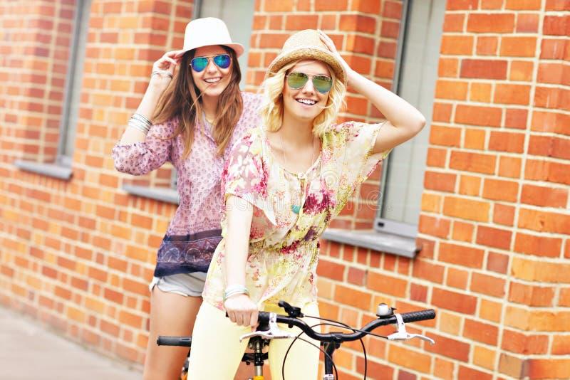 Dos amigas que montan la bicicleta en tándem imagenes de archivo