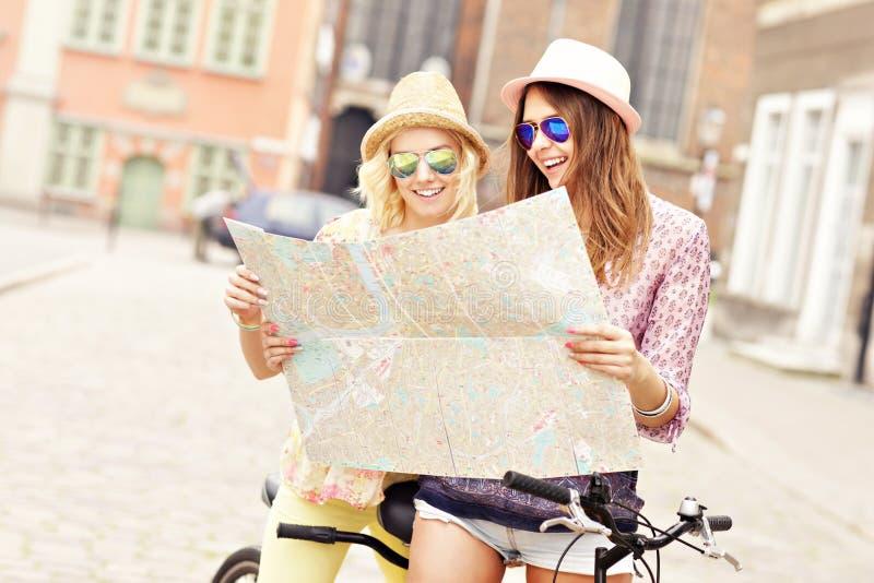 Dos amigas que usan el mapa mientras que monta la bicicleta en tándem imagen de archivo libre de regalías
