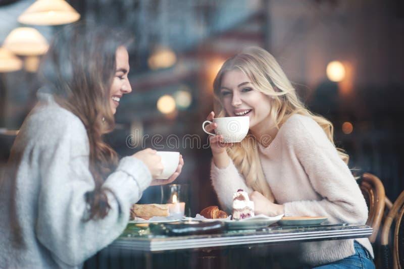 Dos amigas trinking el café en el café y pasan el tiempo junto fotografía de archivo