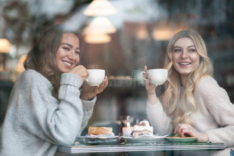 Dos amigas trinking el café en el café y pasan el tiempo junto fotografía de archivo libre de regalías