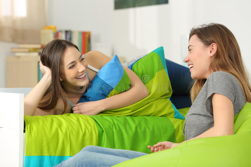 Dos amigos adolescentes que hablan en un dormitorio imágenes de archivo libres de regalías