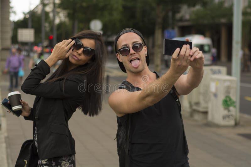 Dos amigos alegres que toman las fotos de ellos mismos en el teléfono elegante foto de archivo libre de regalías