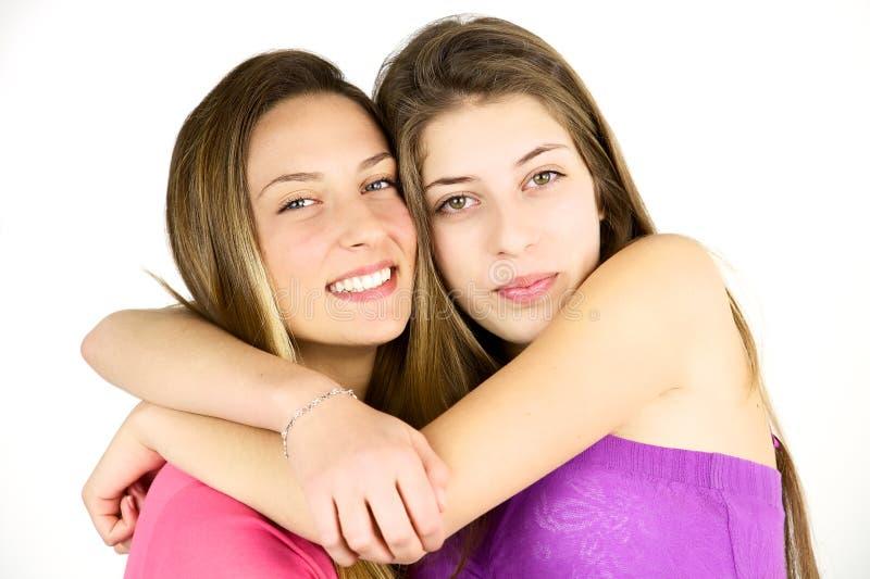 Dos amigos cariñosos del adolescente que abrazan y que miran la cámara aislada imagen de archivo