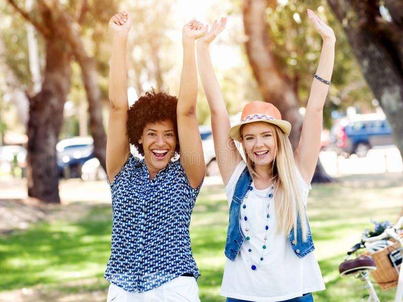 Dos amigos de las mujeres en parque fotografía de archivo