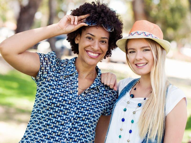 Dos amigos de las mujeres en parque fotografía de archivo libre de regalías