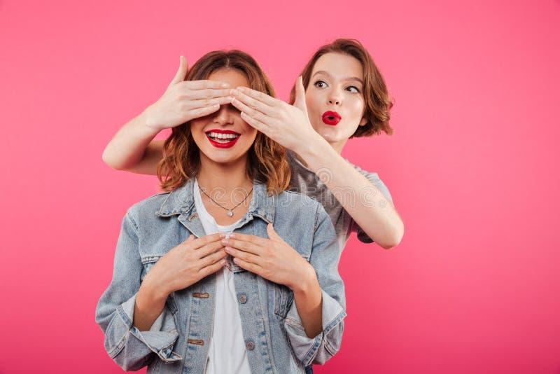 Dos amigos de las mujeres que cubren ojos con las manos fotografía de archivo libre de regalías