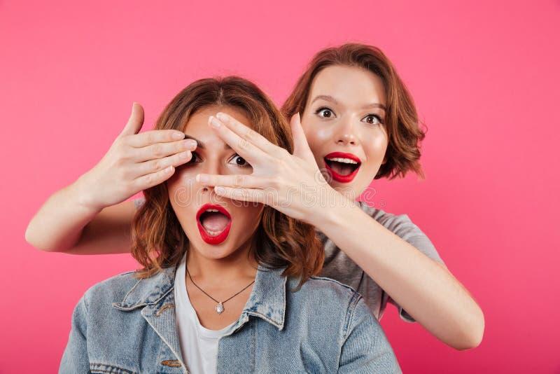Dos amigos de las mujeres que cubren ojos con las manos fotos de archivo