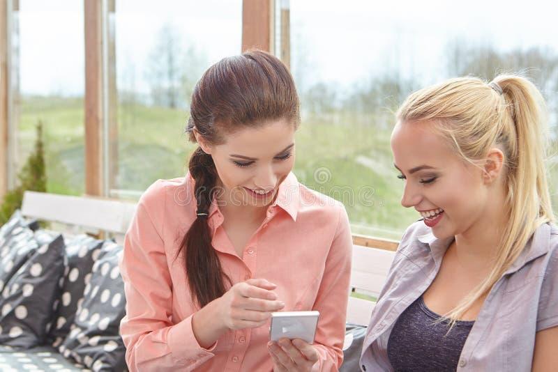 Dos amigos de las mujeres que hablan sosteniendo las tazas de café fotografía de archivo libre de regalías