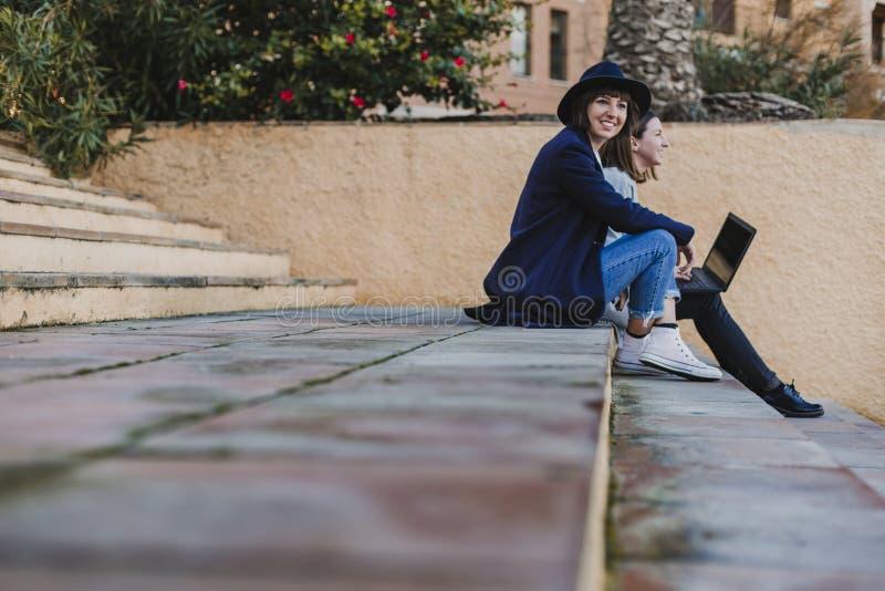 Dos amigos de las mujeres que se sientan en las escaleras al aire libre usando el ordenador port?til y que se divierten fotografía de archivo libre de regalías