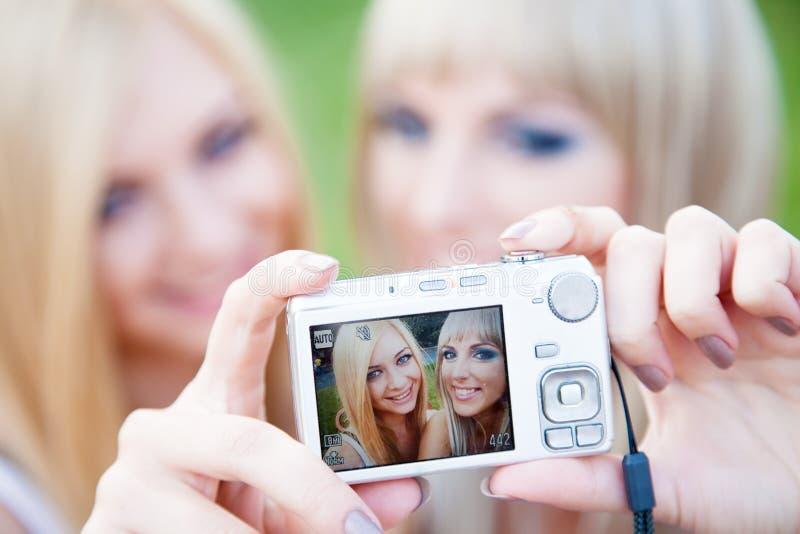 Dos amigos de muchacha con una cámara de la foto fotos de archivo libres de regalías