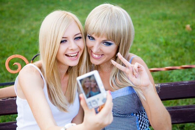Dos amigos de muchacha con una cámara de la foto foto de archivo libre de regalías
