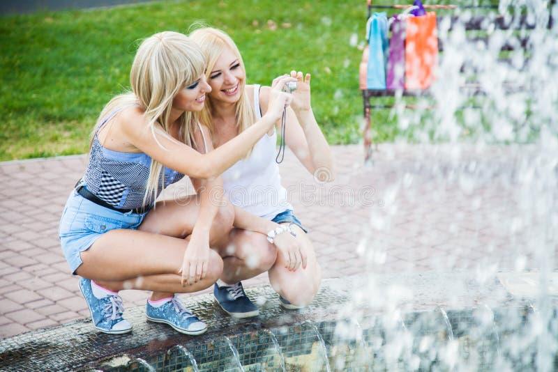 Dos amigos de muchacha con una cámara de la foto fotografía de archivo libre de regalías