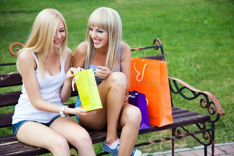 Dos amigos de muchacha hermosos con los bolsos de compras fotos de archivo libres de regalías