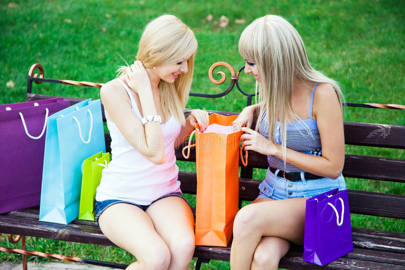 Dos amigos de muchacha hermosos con los bolsos de compras foto de archivo
