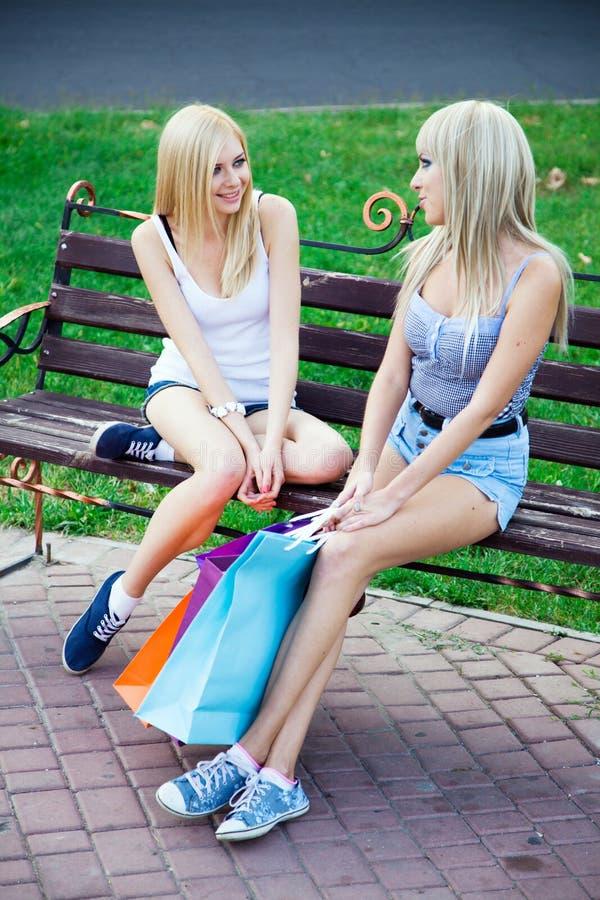 Dos amigos de muchacha hermosos con los bolsos de compras imagenes de archivo