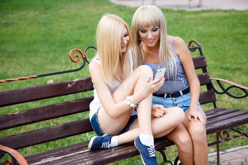 Dos amigos de muchacha que usan un smartphone imagen de archivo libre de regalías