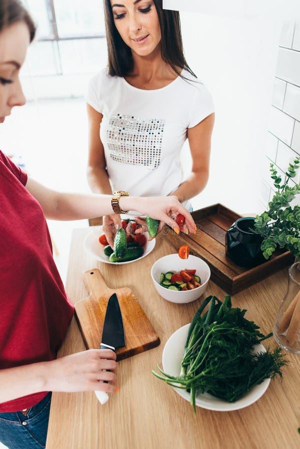 Dos amigos de muchachas que preparan la cena en la cocina que cocina la ensalada imágenes de archivo libres de regalías