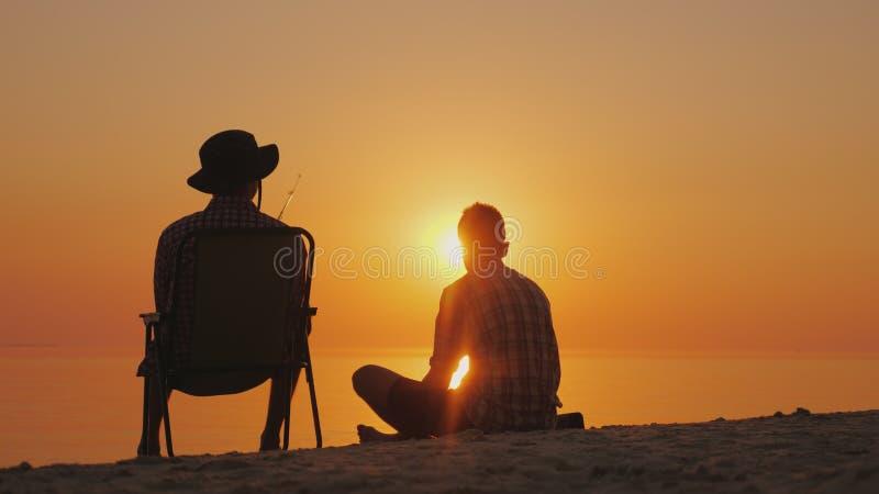 Dos amigos descansan sobre la orilla del lago en la puesta del sol, pescando Amistad y relajación en el aire abierto imágenes de archivo libres de regalías