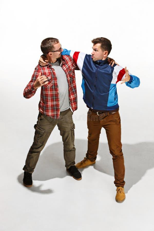 Dos amigos en el desgaste colorido casual que se une y que ríe imagenes de archivo